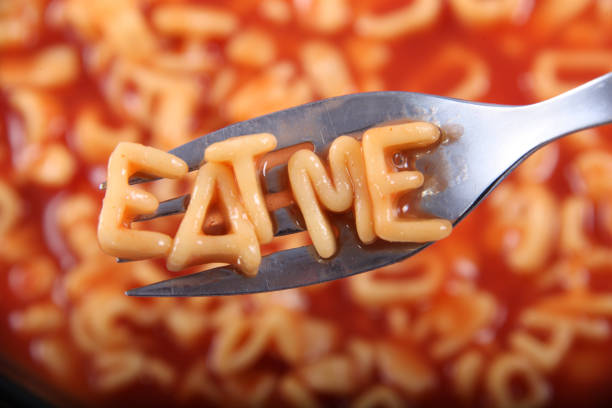 Spaghetti letter spelling the word 'Eat Me' with the letters held up on a fork. stock photo