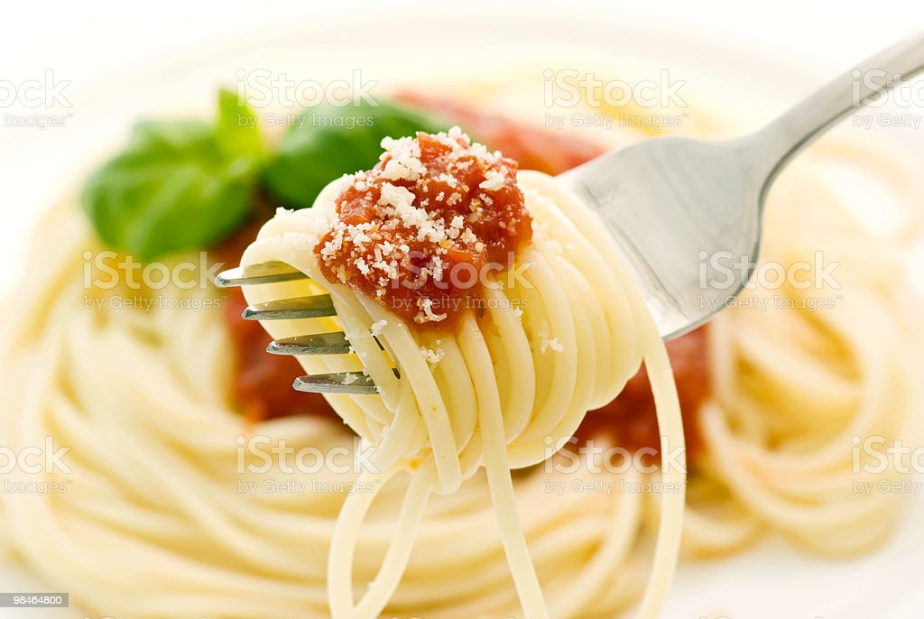 Spaghetti Napoli is rolled around a fork above the dish royalty-free stock photo