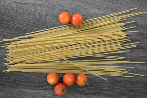 회색 테이블에 빨간 칵테일 토마토와 스파게티 국수 - 배경으로 사용할 수 있습니다 스톡 사진