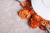 Close up of spaghetti and meatballs under an upside down plate on beige brand new carpet; copy space