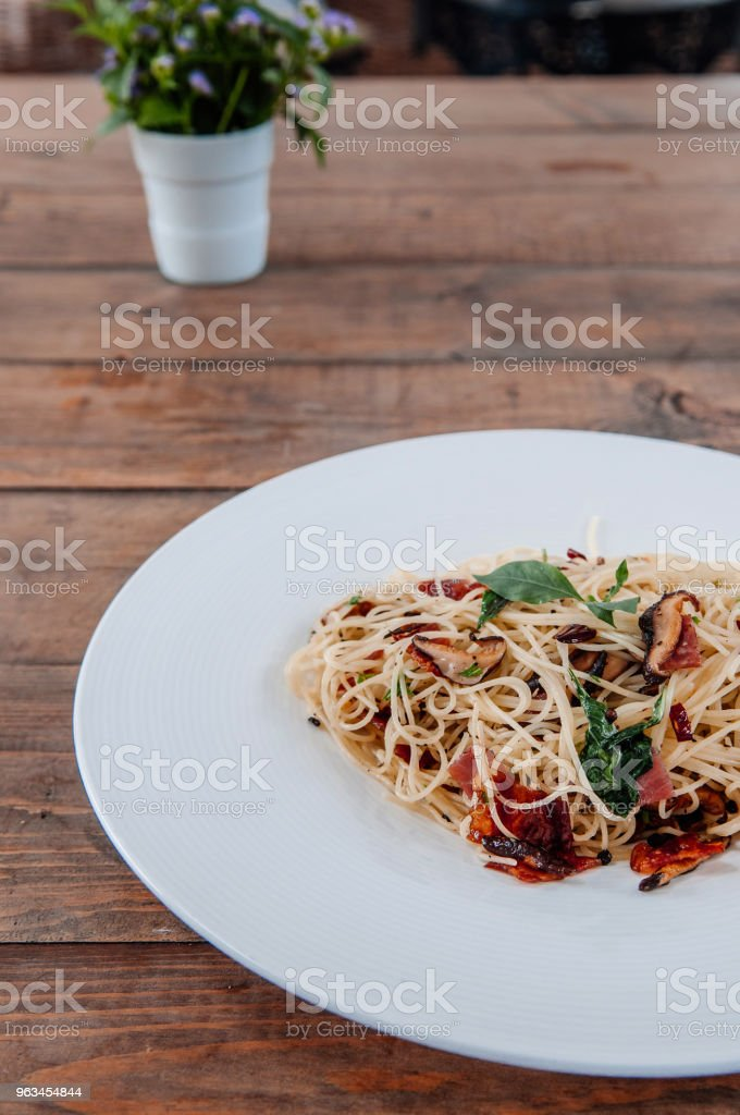 Spaghetti pasta bacon with dried spicy chilli on white plate on the wood table from side view - Zbiór zdjęć royalty-free (Bazylia)