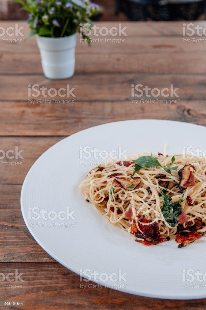 Spagetti makarna pastırma yan görünümden ahşap masa üzerinde beyaz plaka üzerinde kurutulmuş baharatlı biber ile - Royalty-free Acı Biber Stok görsel