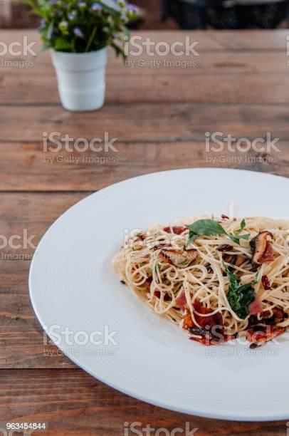 Spaghetti Makaron Boczek Z Suszonymi Pikantne Chili Na Białym Talerzu Na Drewnianym Stole Z Boku - zdjęcia stockowe i więcej obrazów Bazylia