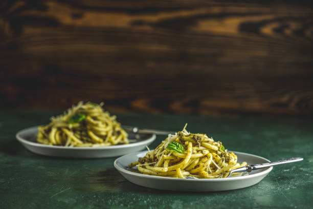 Spaghetti pasta bucatini with pesto sauce and parmesan. Italian traditional perciatelli pasta by genovese pesto sauce in two gray dishes stock photo