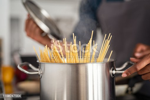 Closeup of spaghetti in pot on stove. Woman holding pot with spaghetti in hot boiling water. Spaghetti ready to be cooked at home.