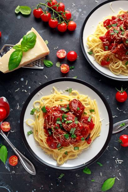 spaghetti nudeln hackfleischbällchen mit tomatensauce, basilikum, kräuter-parmesan-käse auf dunklem hintergrund - spaghetti tomatensauce stock-fotos und bilder
