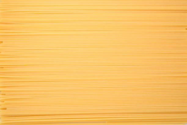 Spaghetti Pasta Textured Background Spaghetti forming a textured background with a striped pattern uncooked pasta stock pictures, royalty-free photos & images