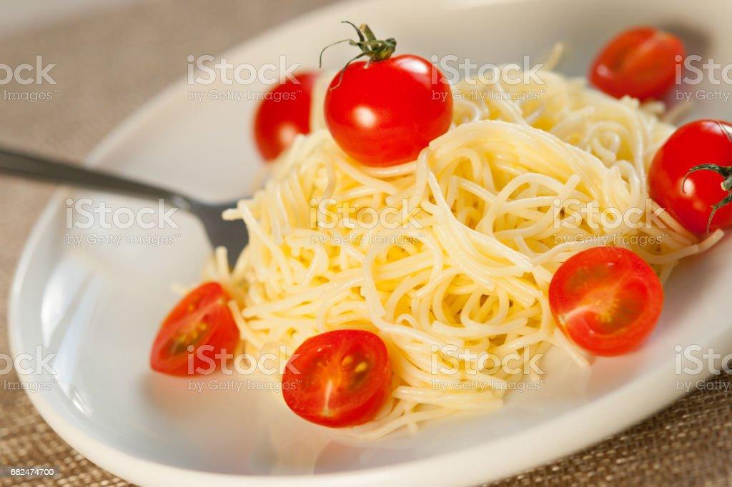 Spaghetti pasta with fresh cherry tomatoes and fork Стоковые фото Стоковая фотография
