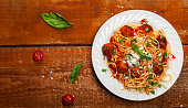 Spaghetti pasta with meatballs and tomato sauce on wooden background, top view