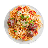 Spaghetti with meatballs, parmesan and tomato sauce on a plate. Tasty Italian pasta food. Top view shot above isolated on white background.