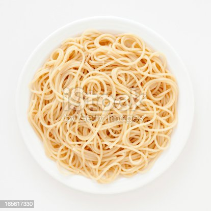 Top view of white dish with boiled spaghetti over it