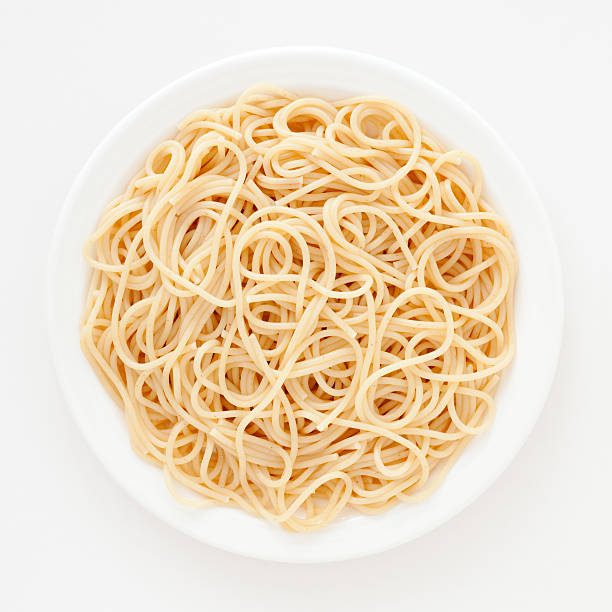 Spaghetti Top view of white dish with boiled spaghetti over it spaghetti stock pictures, royalty-free photos & images