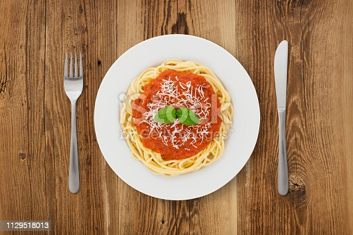 Spaghetti plate with knife and fork on wooden background