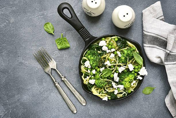 spaghetti  primavera with green spring vegetables and feta cheese.top view. - spaghetti mit spinat stock-fotos und bilder