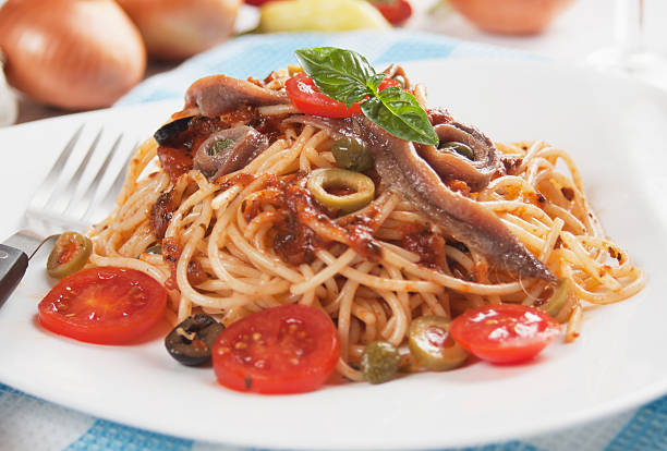 """Spaghetti puttanesca """"Spahgetti a la puttanesca with anchovy, caper, tomato and olives"""" anchovy stock pictures, royalty-free photos & images"""