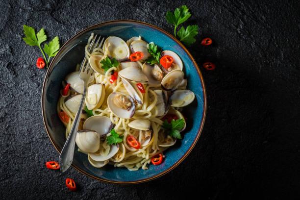 spaghetti vongole med musslor, paprika och persilja på black rock - pasta vongole bildbanksfoton och bilder