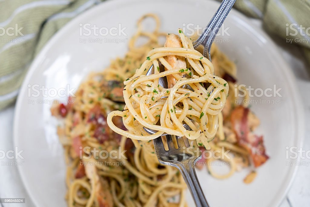 Spaghetti with bacon and basil on on a fork roll. royalty-free stock photo