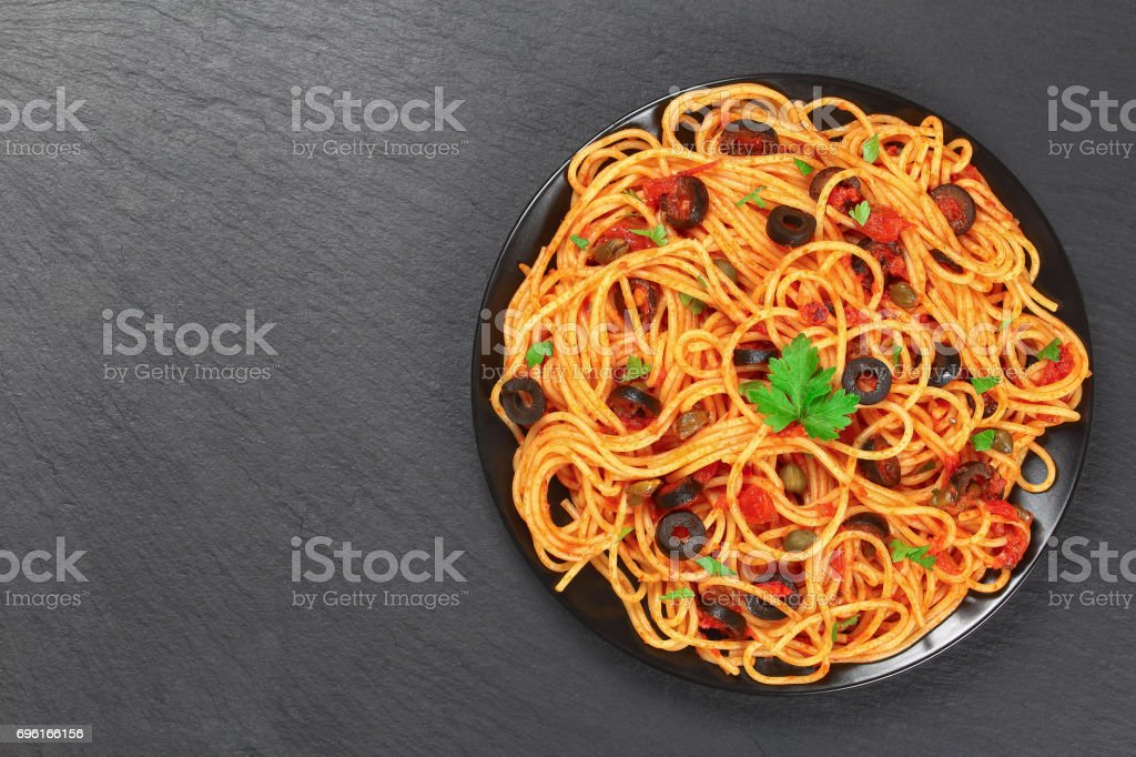 Spaghetti with capers. olives, anchovies, tomato sauce stock photo