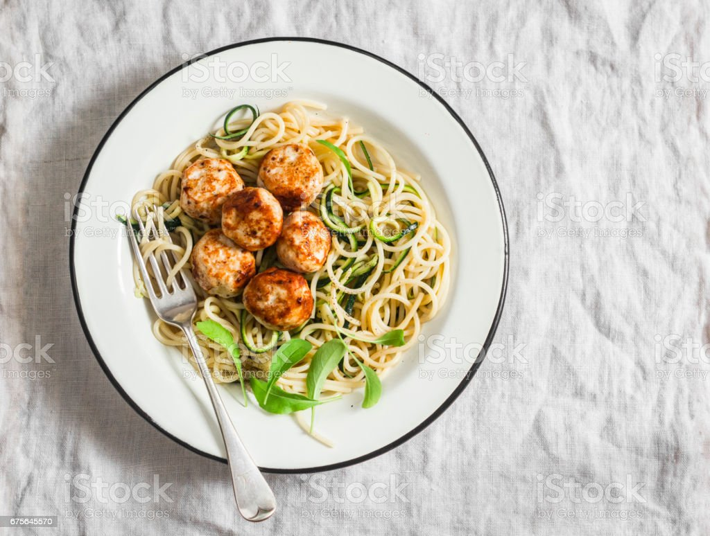 Spaghetti with cheesy chicken meatballs and zucchini noodles. Delicious lunch on a light background, top view royalty-free stock photo