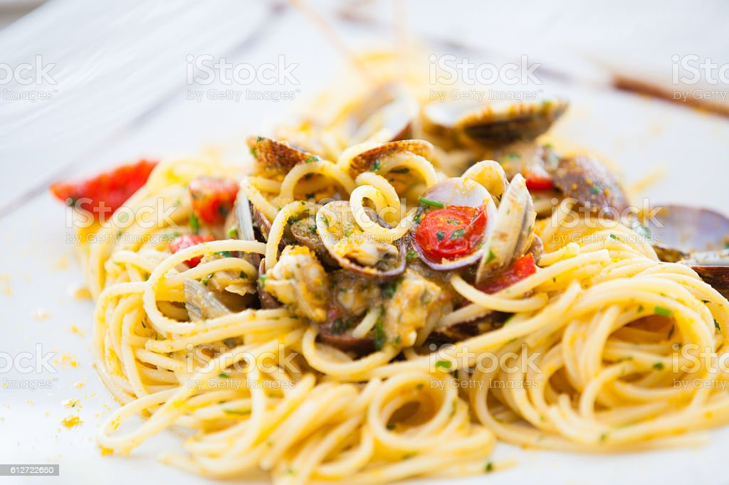 Spaghetti with clams, bottarga and fresh tomatoes stock photo