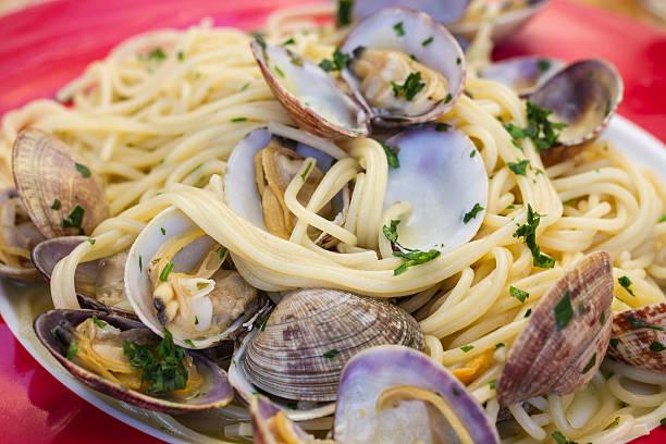 spaghetti mit venusmuscheln - muscheln zubereiten stock-fotos und bilder