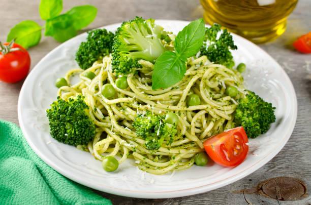 spaghetti mit grünen erbsen und basilikum-pesto - spaghetti mit spinat stock-fotos und bilder