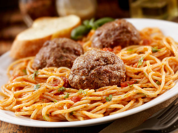 Spaghetti with Large Meatballs Spaghetti with Large Meatballs in a Tomato Basil Sauce with freshly grated Parmesan cheese -Photographed on Hasselblad H3-22mb Camera meatball stock pictures, royalty-free photos & images