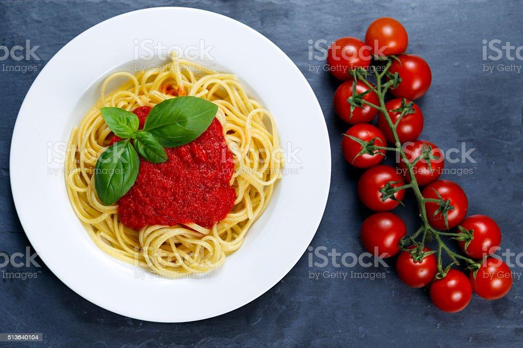 Spaghetti with marinara sauce and basil leaves on top stock photo