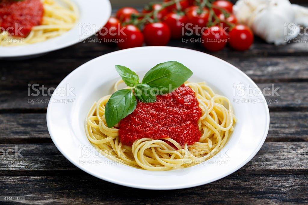 Spaghetti with marinara sauce and basil leaves on top. stock photo