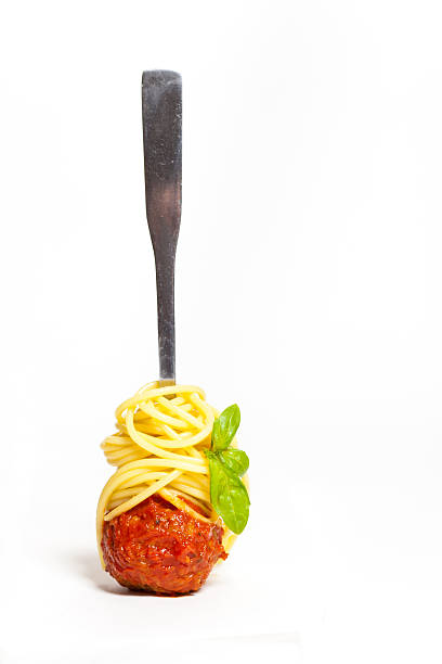 Spaghetti with meatball twirled neatly around a fork Meatball with spaghetti and basil on a fork meatball stock pictures, royalty-free photos & images