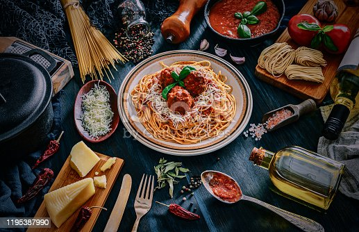 Spaghetti with meatballs and and ingredients on rustic pots. Shot taken on wooden bluish table in rustic kitchen