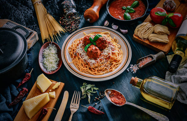 Spaghetti with meatballs and and ingredients on rustic pots. Shot taken on wooden bluish table in rustic kitchen stock photo