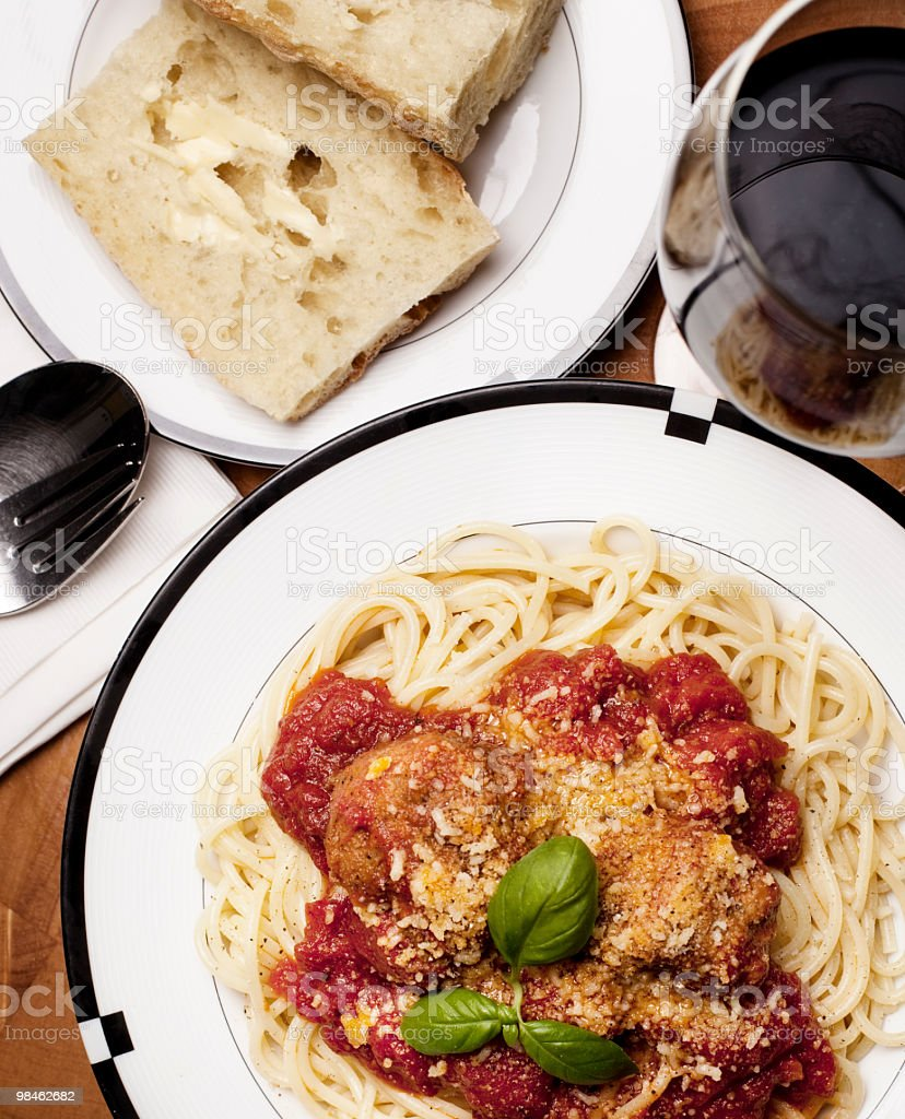 Spaghetti with meatballs, French bread and red wine from above royalty-free stock photo