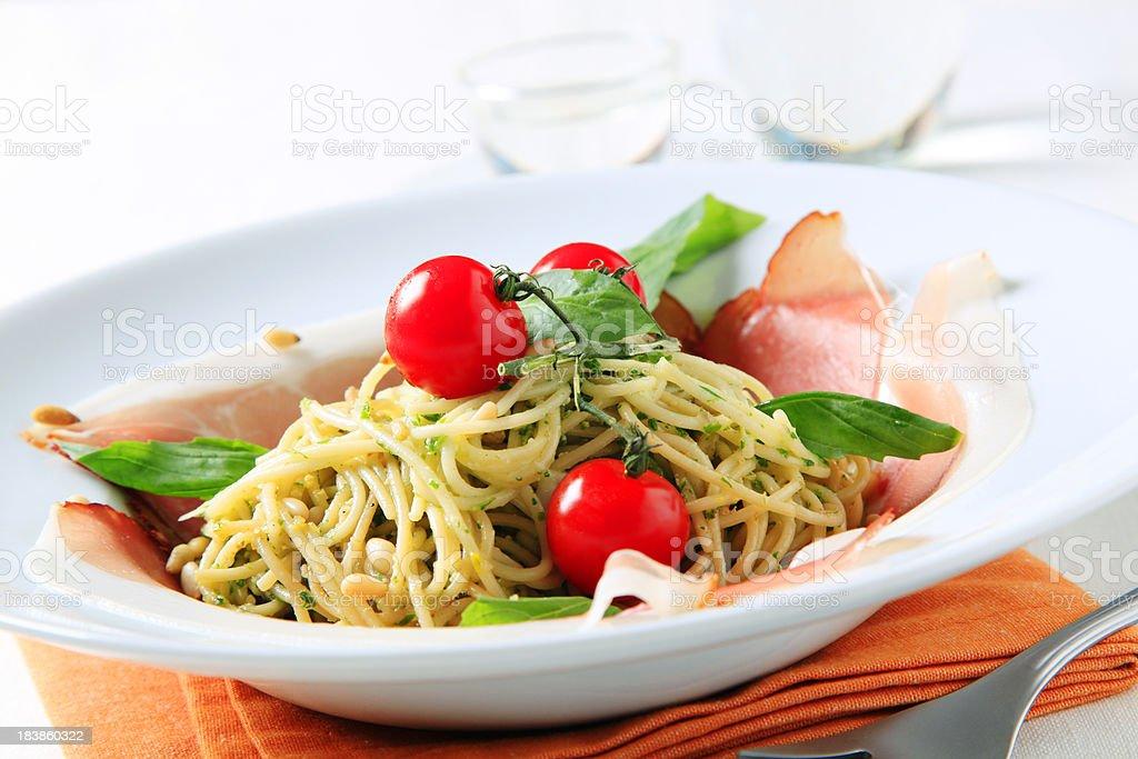 Spaghetti with pesto, pine nuts and Parma ham royalty-free stock photo