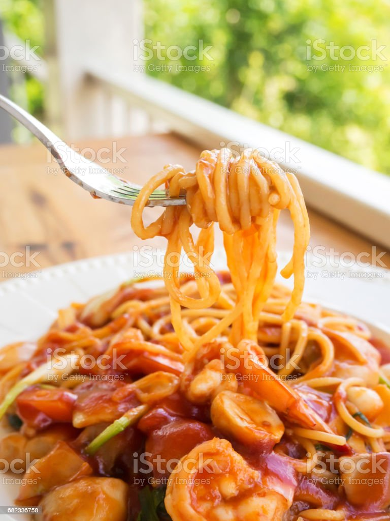 Spaghetti with red sauce and shrimp on white plate. Tasty noodle. High nutrition. Action of fork ladle spaghetti over plate. zbiór zdjęć royalty-free