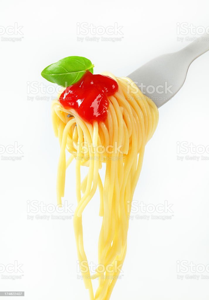 spaghetti with sauce and basil hanging on a fork royalty-free stock photo