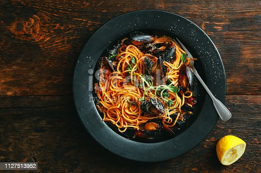 Spaghetti with smoky tomato & seafood sauce on dark blue background