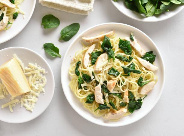 espaguetis con hojas de espinacas, rodajas de pechuga de pollo asada y queso rallado - pasta fotografías e imágenes de stock