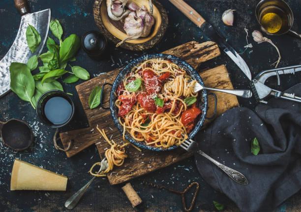 espaguete com tomate e manjericão e ingredientes para fazer macarrão - comida italiana - fotografias e filmes do acervo