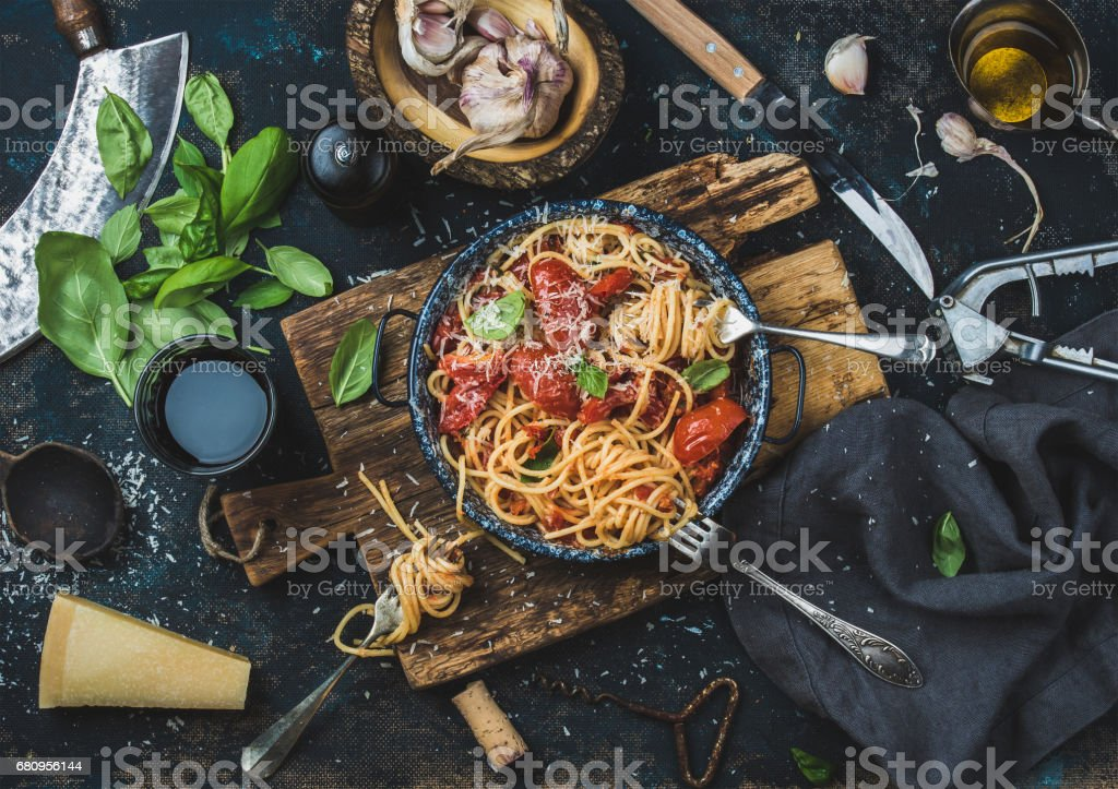 Spaghetti with tomato and basil and ingredients for making pasta stock photo
