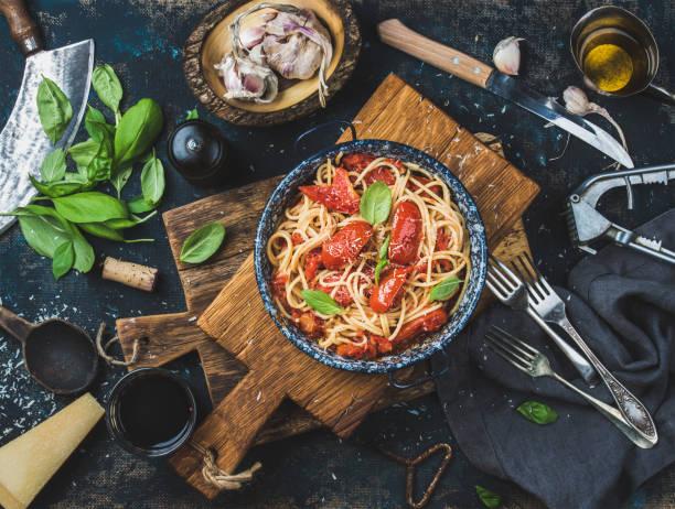spaghetti mit tomaten und basilikum in platte auf holzbrett - weinsoße stock-fotos und bilder