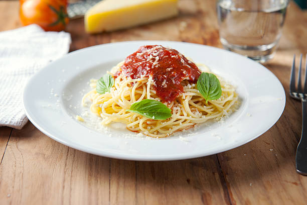 spaghetti mit tomatensauce auf platte auf holzbrett - spaghetti tomatensauce stock-fotos und bilder