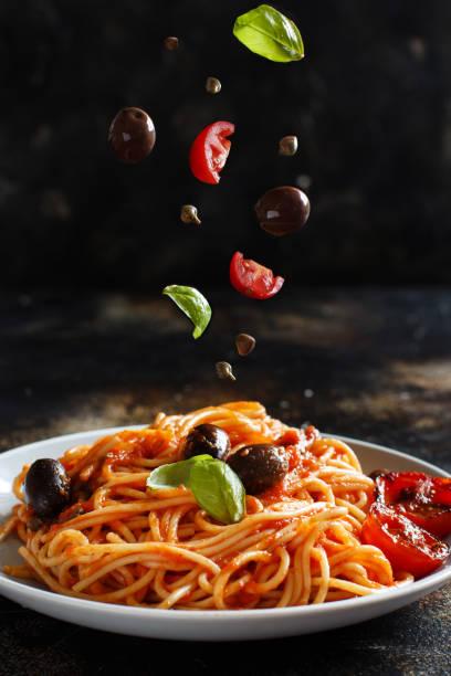 domates sosu zeytin ve kapanlar ile spagetti - i̇talyan mutfağı stok fotoğraflar ve resimler