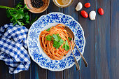 Spaghetti with tomato sauce on wooden table