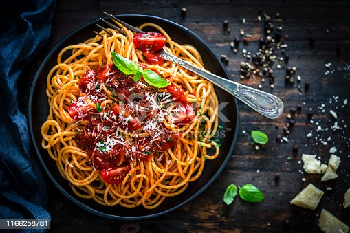Top view of spaghetti with tomato sauce plate shot on rustic wooden table. A vintage fork is inside the plate. Predominant color is red. Low key XXXL 42Mp studio photo taken with SONY A7rII and Sony FE 90mm f2.8 Macro G OSS lens
