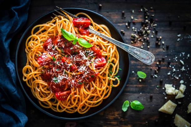 espaguete com o molho de tomate disparado na tabela de madeira rústica - comida italiana - fotografias e filmes do acervo
