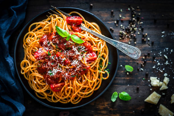 espaguetis con salsa de tomate rodado según una mesa de madera rústica - pasta fotografías e imágenes de stock