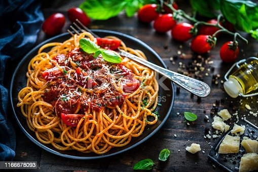 High angle view of spaghetti with tomato sauce plate shot on rustic wooden table. Some ingredients like ripe tomatoes, olive oil, basil, peppercorns and Parmesan cheese are all around the plate. XXXL 42Mp studio photo taken with SONY A7rII and Sony FE 90mm f2.8 Macro G OSS lens