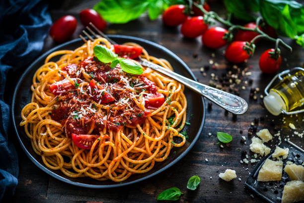 Spaghetti with tomato sauce shot on rustic wooden table High angle view of spaghetti with tomato sauce plate shot on rustic wooden table. Some ingredients like ripe tomatoes, olive oil, basil, peppercorns and Parmesan cheese are all around the plate. XXXL 42Mp studio photo taken with SONY A7rII and Sony FE 90mm f2.8 Macro G OSS lens spaghetti stock pictures, royalty-free photos & images