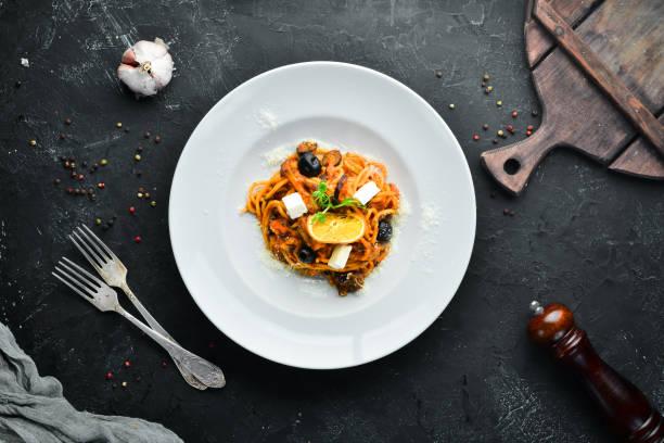 Espaguete com tomates, azeitonas e queijo do feta em uma placa. Vista superior. Espaço livre para o seu texto. - foto de acervo